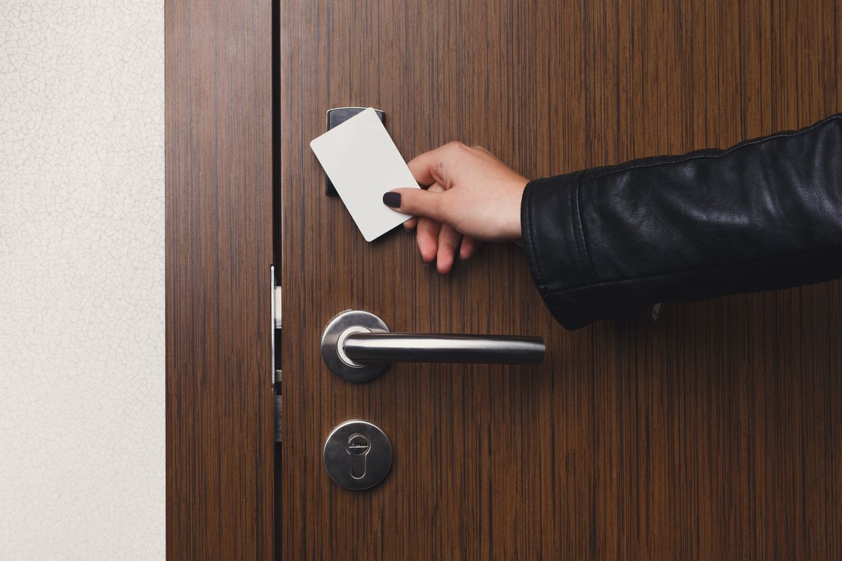 Hand inserting key card in electronic lock. Woman opening hotel room door. Privacy, security, personal identification concept, copy space